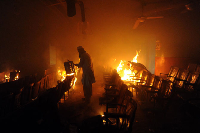 A Pakistani demonstrator carries material inside a burning cinema during a protest against an anti-Islam film in Peshawar on September 21, 2012.