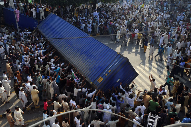 Pakistani demonstrators topple a freight container, placed by police to block a street during a protest against an anti-Islam film in Lahore on September 21, 2012.