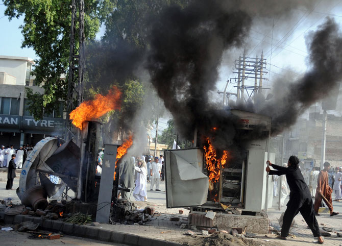 Pakistani demonstrators vandalise machinery during a protest against an anti-Islam film in Peshawar on September 21, 2012.
