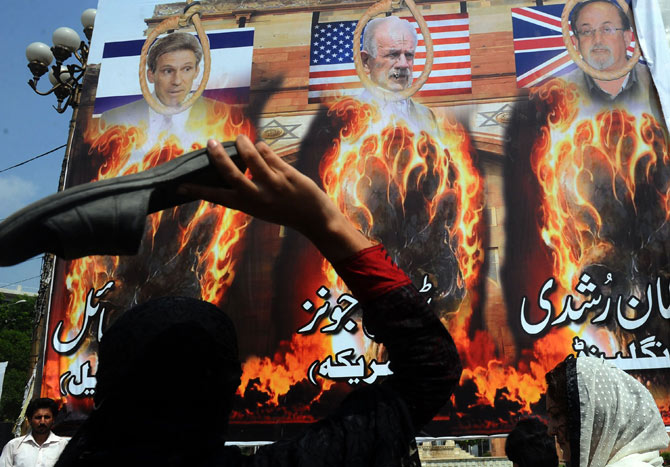 Pakistani demonstrators throw their shoes towards a portrait of Florida pastor Terry Jones (C) during a protest against an anti-Islam film in Lahore on September 21, 2012.