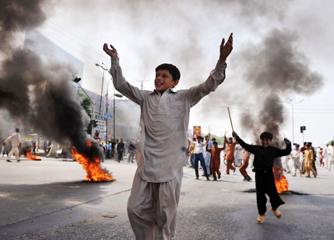 Pakistani demonstrators react beside burning tyres as they block a main highway during a protest against an anti-Islam film in Rawalpindi on September 21, 2012.