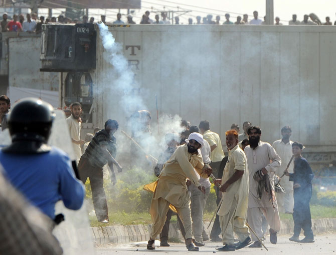 A Pakistani demonstrator throws a tear gas shell towards riot police during a protest against an anti-Islam film in Islamabad on September 21, 2012.