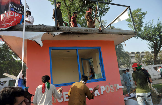 Pakistani demonstrators attack an empty police post as they attempt to reach the US embassy during a protest against an anti-Islam film in Islamabad on September 21, 2012.