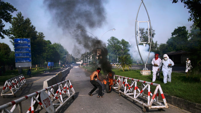 A Pakistani protester, center, pushes a burning tire as others run away to avoid tear gas fired by riot police during clashes erupted as protestors tried to approach the US embassy, in Islamabad, Pakistan, Friday, Sept. 21, 2012.