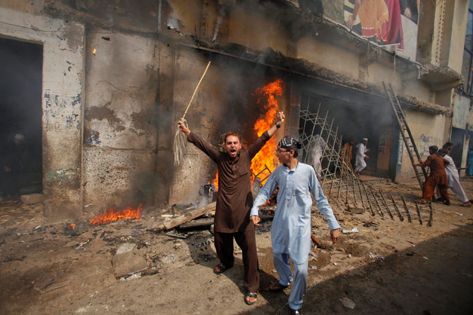 A protester holds a stick as he shouts anti-American slogans in front of a burning cinema during an anti-US protest rally to mark the ?Day of Love? in Peshawar September 21, 2012.