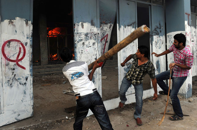 Pakistani demonstrators attack a cinema during a protest against an anti-Islam film in Karachi on September 21, 2012.
