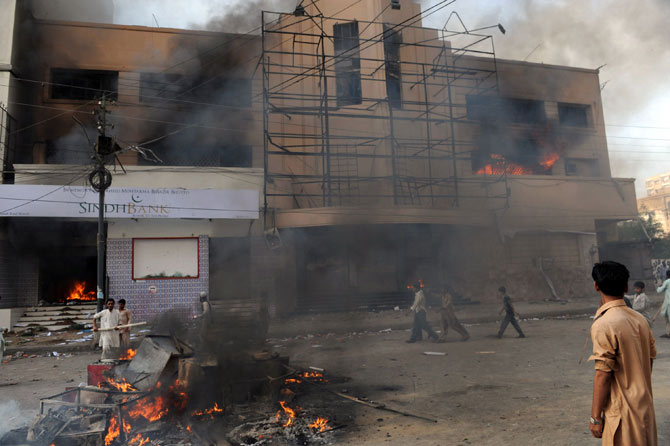 Pakistani demonstrators are pictured in front of a burning cinema during a protest against an anti-Islam film in Karachi on September 21, 2012.