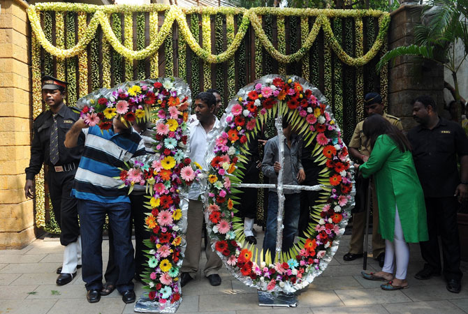 Indian security guards inspect a floral arrangement in the shape of the number seventy at the entrance of Bollywood actor Amitabh Bachchan residence on his 70th birthday in Mumbai on October 11, 2012.  ? Photo by AFP