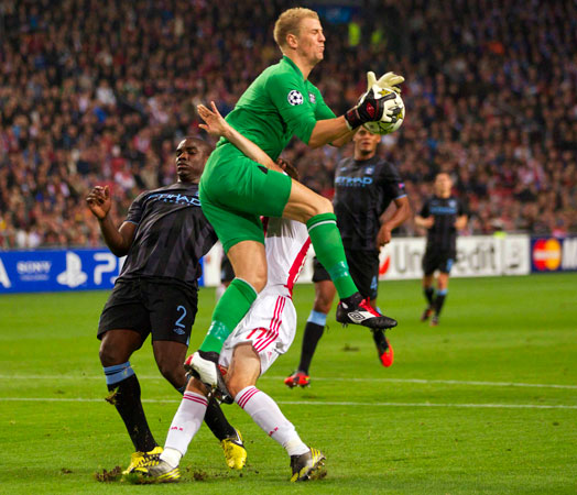 Daley Blind (bottom) of Ajax Amsterdam fights for the ball with goalkeeper Joe Hart of Manchester City during their Champions League Group D soccer match at the Amsterdam Arena in Amsterdam. – Photo by Reuters