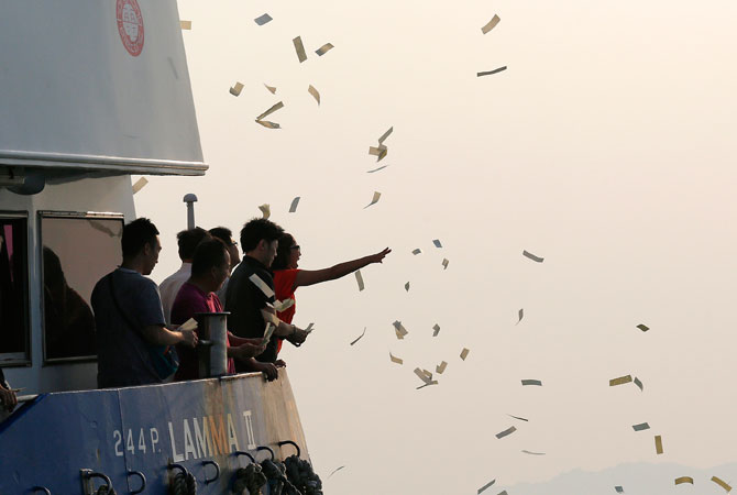 Relatives of the victims throw paper money Tuesday, Oct. 2, 2012 as they pay tribute to the ill-fated people aboard a boat that sank Monday night near Lamma Island, off the southwestern coast of Hong Kong Island. ? Photo by AP