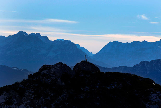 A hiker rests near a cross as he enjoys the view over the Alps near the top of Wendelstein mountain 1,838 meters; near Bayrischzell, southern Germany. ? Photo by AP