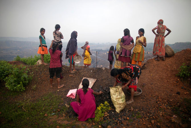 Local women stand atop of an open cast coal field as other collect coal at Dhanbad district in the eastern Indian state of Jharkhand.