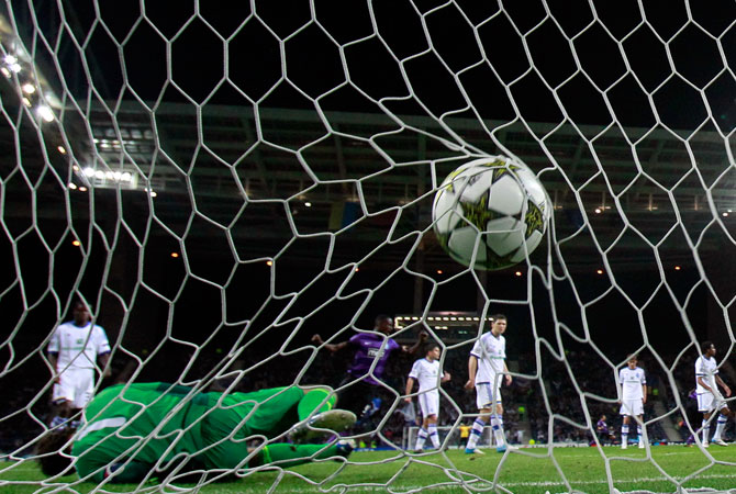 FC Porto's Jackson Martinez, from Colombia, center, scores their second goal past Dynamo Kiev's goalkeeper Olexandr Shovkovskiy, on the ground, during their Champions League group A soccer match at the Dragao stadium in Porto. – Photo by AP