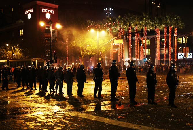 Police officers try to disperse San Francisco Giants fans celebrating their team's winning of the World Series. ? Photo by AFP