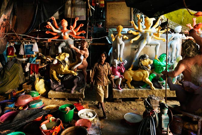 An artist walks by idols of Hindu warrior goddess. ? Photo by AP