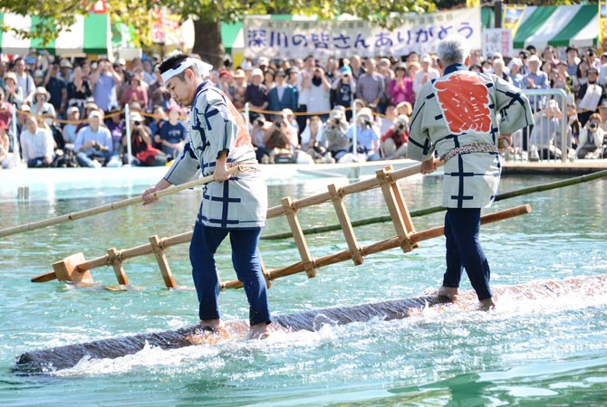 Raftsmen, members of the Kiba 'kakunori' preservation society, perform a stunt on a floating square timber at a local festival in Tokyo. The stunt derived from lumberjacks' daily work in the Edo period (1603-1868), when they made rafts with fire-hooks in their hands standing on floating lumbers. ?AFP  Photo