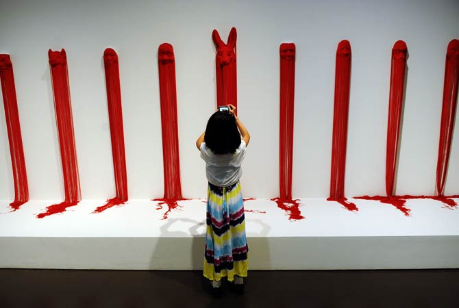 A child takes photos of artwork during a preview visit to The China Art Museum. ? Photo by AFP