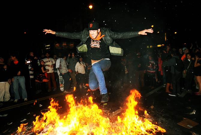 A San Francisco Giants fan jumps over a bonfire in San Francisco's Mission district. ? Photo by AFP