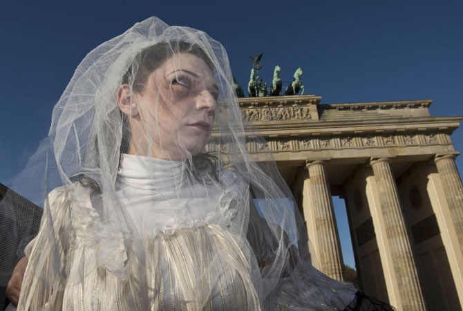 A performer dressed like a bride with horror-like make-up acts in front of Brandenburg Gate in Berlin, Germany. ? Photo by AFP