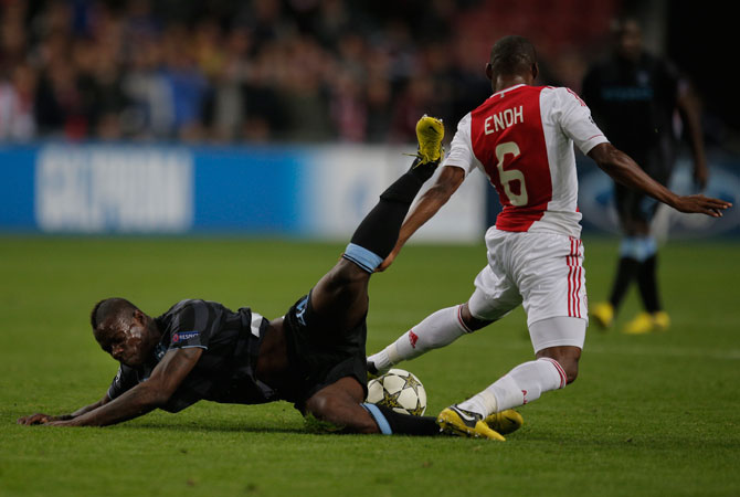 Manchester City player Mario Balotelli falls when tackled by Ajax player Eyong Enoh, right, during the Champions League Group D soccer match at ArenA stadium in Amsterdam, Netherlands. – Photo by AP