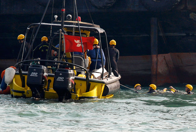 Frogmen from firefighting team retrieve a body, right, near a boat, unseen, after it collided and sank Monday night near Lamma Island, off the southwestern coast of Hong Kong Island. ? Photo by AP