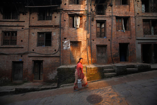 A woman carrying a milk jar walks along a street in the ancient Nepalese city of Bhaktapur.