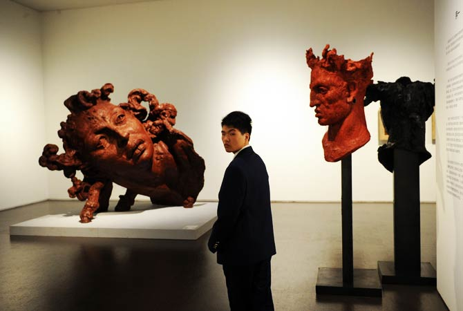 A security guard stands near sculptures during a preview visit. ? Photo by AFP