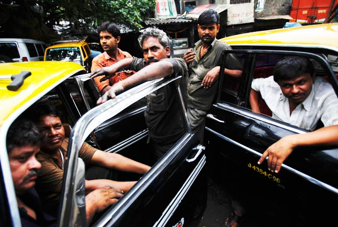 Drivers and mechanics of Premier Padmini taxis gather together at a workshop. ? Photo by Reuters