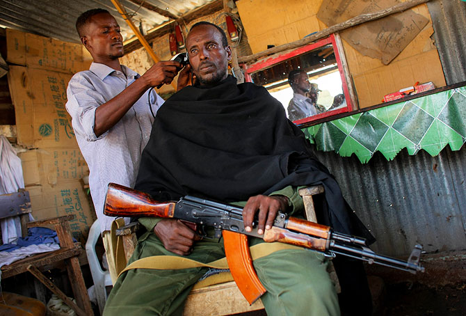 A fighter of the pro-government Ras Kimboni Brigade gets a haircut inside a barber's kiosk in a market area in the centre of the southern Somali port city of Kismayo.
