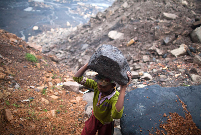 A boy carries a piece of coal at an open cast coal field at Dhanbad district in the eastern Indian state of Jharkhand.