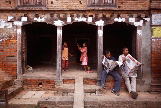 Children sing and dance while men read newspapers in the ancient Nepalese city of Bhaktapur.