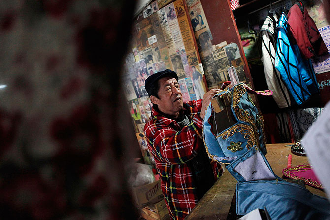 Mexican former bullfighter and tailor to bullfighters Roberto 'Gironcito' Morales works on a matador's outfit in Mexico City August 28, 2012.