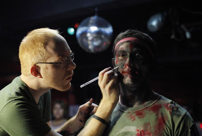 A man dressing up as a zombie has make up applied on him during an event in New York.?Reuters Photo