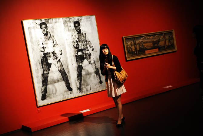 A woman walks past artwork of Elvis Presley (L) by US artist Andy Warhol. ? Photo by AFP