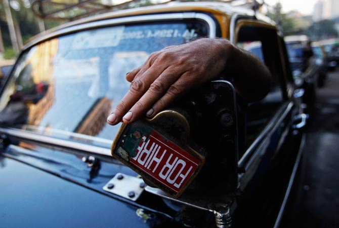 A driver demonstrates the use of a manually operated fare meter on his taxi. ? Photo by Reuters