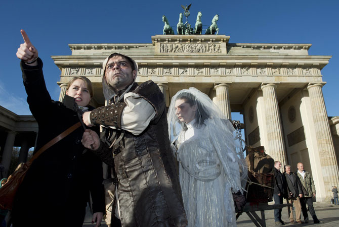 A young woman reacts as a performer dressed in a medieval costume and horror-like make-up approaches her with a pincer in front of Brandenburg Gate in Berlin, Germany.  ? Photo by AFP