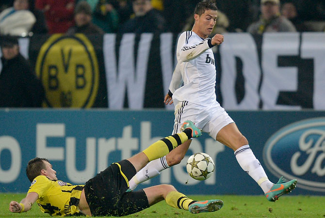 Real's Cristiano Ronaldo, right, and Dortmund's Kevin Grosskreutz challenge for the ball during the Champions League Group D soccer match between Borussia Dortmund and Real Madrid in Dortmund, Wednesday. – Photo by