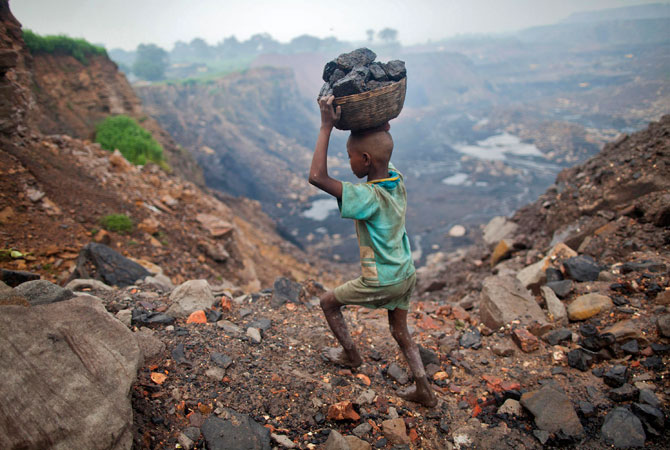 A boy carries coal at an open cast coal field at Dhanbad district in the eastern Indian state of Jharkhand.