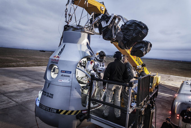 In this image obtained from www.redbullcontentpool.com, pilot Felix Baumgartner (Center) of Austria stands on the step of his capsule during the preparation for the final manned flight of Red Bull Stratos in Roswell, New Mexico. ? Photo by AFP