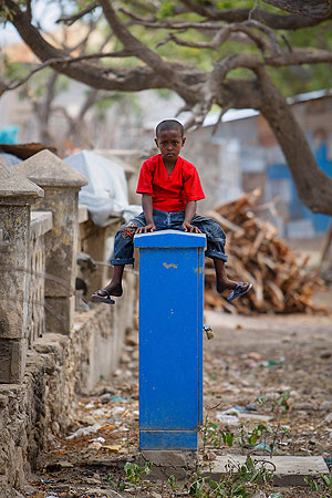 A young Somali boy sits atop a pillar in the centre of the southern Somali port city of Kismayo,  approx. 500km south of the country's capital Mogadishu.