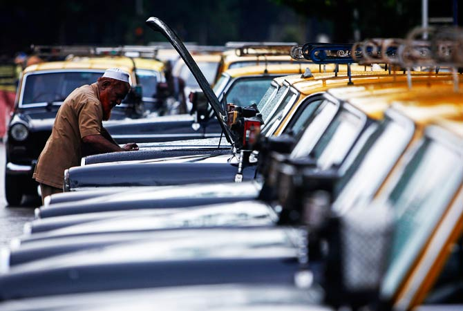 A taxi driver inspects the engine of his taxi at a taxi park. ? Photo by Reuters