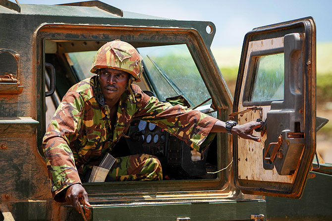 A soldier serving with the Kenyan Contingent of the African Union Mission in Somalia (AMISOM) looks out the door of an armoured personnel carrier in the grounds of Kismayo University in the southern Somali port city of Kismayo.