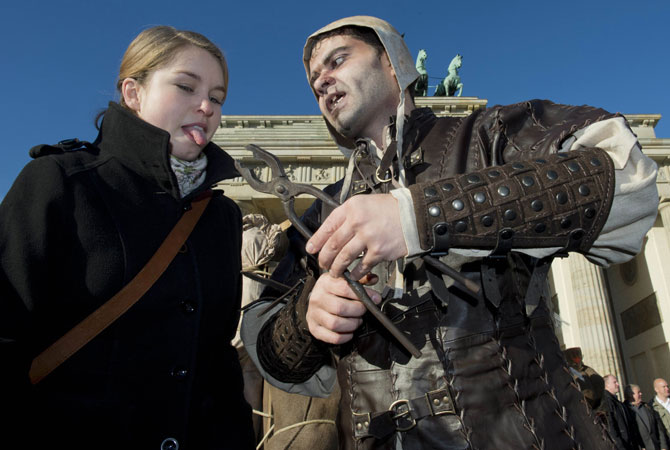 A young woman reacts as a performer dressed in a medieval costume and horror-like make-up approaches her with a pincer in front of Brandenburg Gate in Berlin. ? Photo by AFP