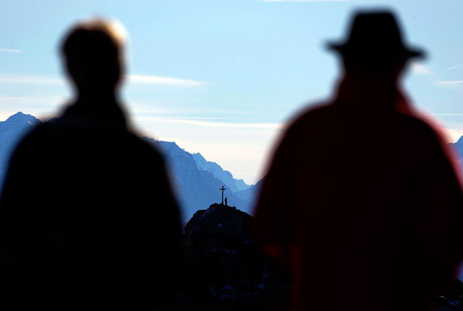 Hikers silhouetted against the Alps near the top of Wendelstein mountain. ? Photo by AP