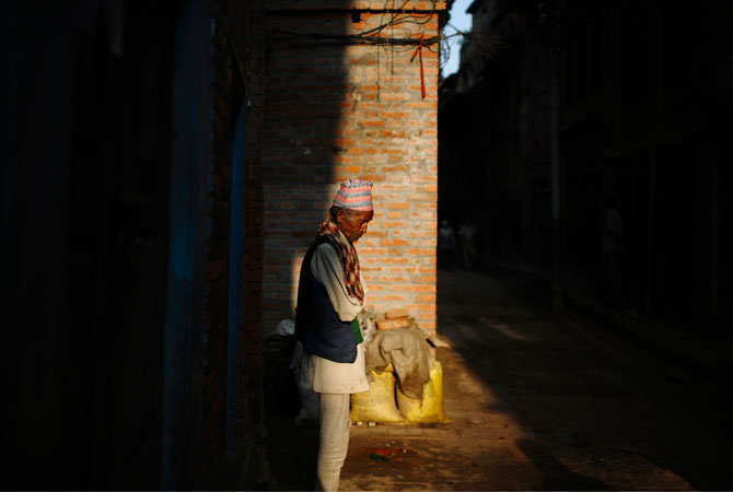 A man stands in the early morning sun in the ancient Nepalese city of Bhaktapur.
