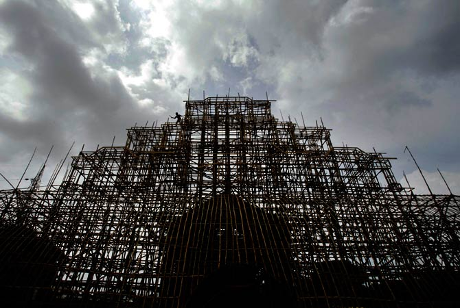 An Indian laborer is seen atop a building under construction at the venue for the upcoming Durga Puja, or Durga Prayers. ? Photo by AP