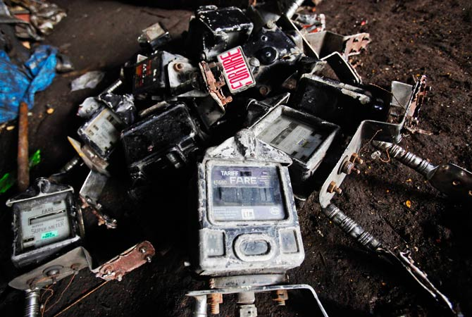 Scrapped fare meters from taxis lie in a pile at a scrap yard. ? Photo by Reuters