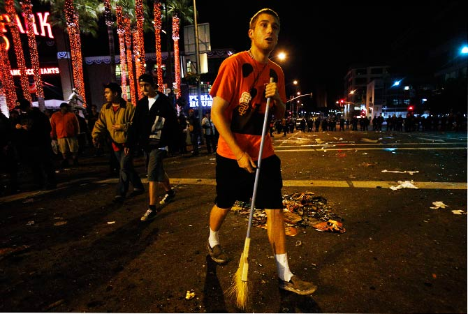 A baseball fan attempts to sweep up broken glass on a street as fans celebrate. ? Photo by Reuters