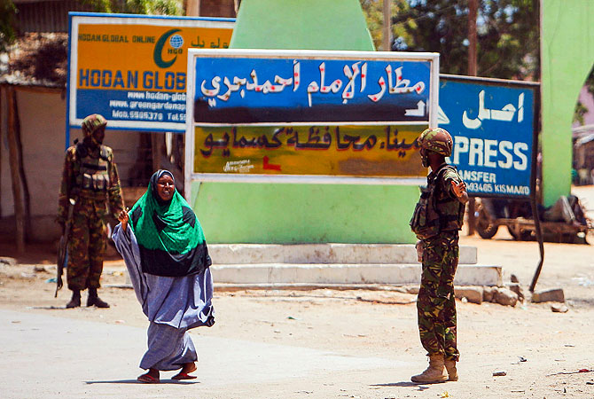Soldiers serving with the Kenyan Contingent of the African Union Mission in Somalia (AMISOM) direct a Somali woman as they patrol along the streets in the centre of the southern Somali port city of Kismayo.