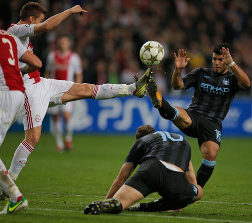 Ajax player Niklas Moisander, left, clears the ball in the penalty box before Sergio Aguero, right, can score during the Champions League Group D soccer match at ArenA stadium in Amsterdam, Netherlands. Ajax won the match with a 3-1 score, bottom is Manchester City player Edin Dzeko. – Photo by AP
